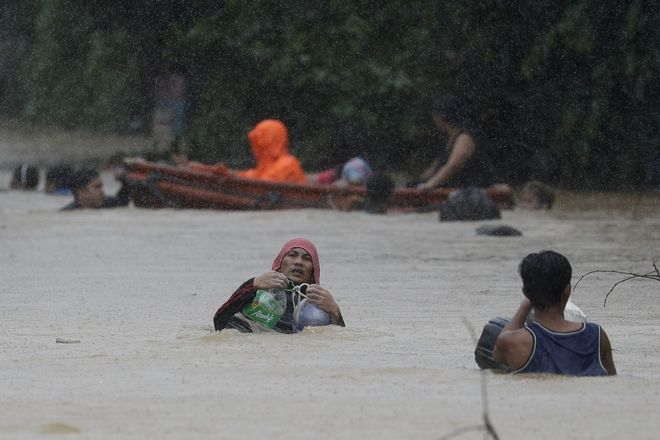 A man uses plastic containers to keep himself afloat as he crosses flooded road in Marikina, Philippines, due to Typhoon Vamco on Thursday, Nov. 12, 2020. The typhoon swelled rivers and flooded low-lying areas as it passed over the storm-battered northeast Philippines, where rescuers were deployed early Thursday to help people flee the rising waters. (AP Photo/Aaron Favila)